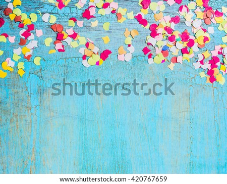 Colorful confetti on  light blue background, border. Party background - stock photo