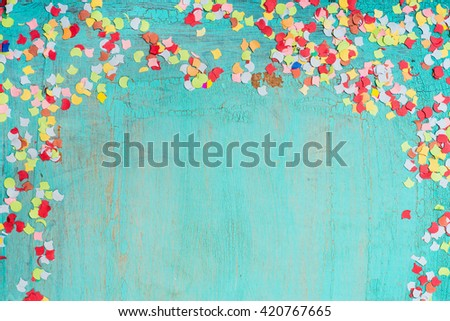 Colorful confetti on  turquoise blue background, border. Party background - stock photo