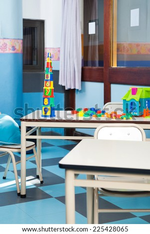 Colorful construction blocks and house on desk in classroom - stock photo