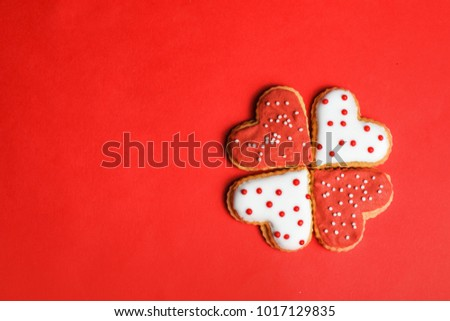 Colorful cookies in heart-shapes on red