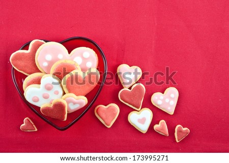 Colorful cookies in heart-shapes on red plate