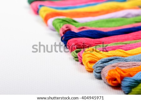Colorful cotton craft threads on white canvas with copy space - stock photo