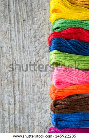 Colorful cotton craft threads on wood background with copy space  - stock photo