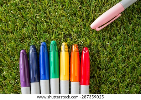 colorful cover marker pen on grass - stock photo