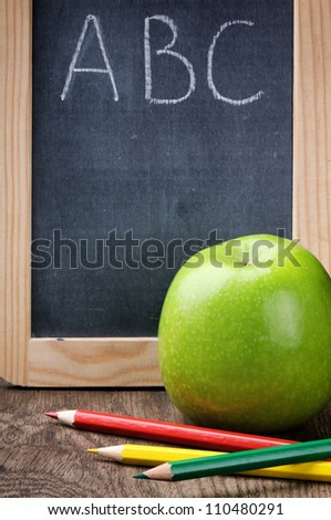 Colorful crayons and apple on wooden desk - stock photo