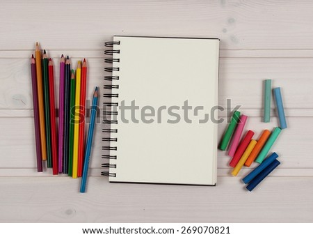 Colorful crayons and sketchpad on wood table - stock photo
