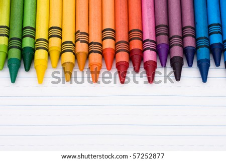 Colorful crayons on a sheet of lined paper, Education background - stock photo
