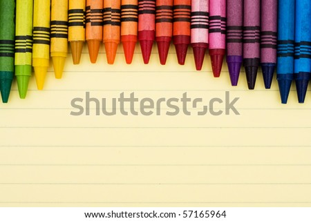 Colorful crayons on a sheet of lined paper, Educational background - stock photo