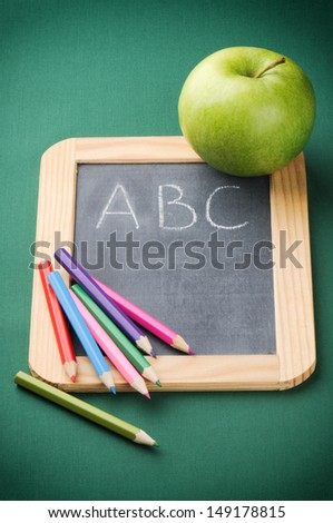 Colorful crayons on blackboard. Back to school concept