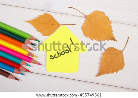 Colorful crayons, shape of building with word school and orange leaves on white boards, back to school in autumn concept