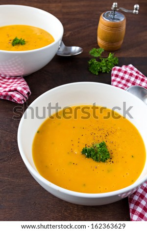 Colorful creamy soup made of pumpkin, sweet potato and coconut milk. Decorated with parsley and fresh ground black pepper. Two servings