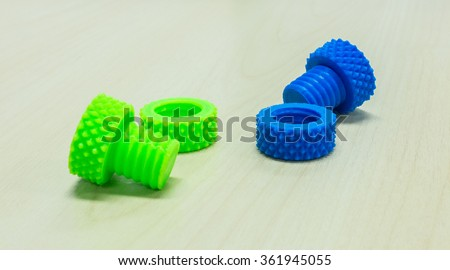 Colorful Creative Plastic Screw Nuts Bolts and Rings made by 3D Printer on Wooden Table - stock photo