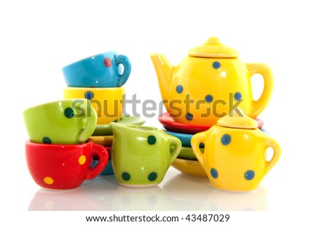 colorful crockery with cups saucers teapot and plates - stock photo