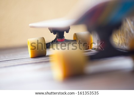 Colorful cruiser skate board with yellow wheels in perspective view - stock photo
