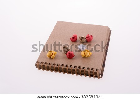 Colorful crumbled paper on a notebook on a white background - stock photo