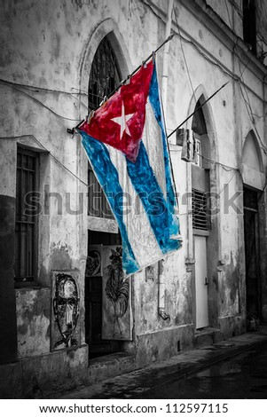 Colorful cuban flag in a shabby black and white street in Havana - stock photo