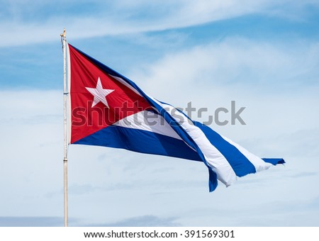 Colorful Cuban flag waiving high in the air, beautiful red, white, blue colors