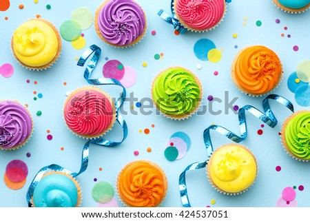 Colorful cupcake party background on blue - stock photo