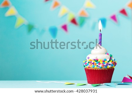 Colorful cupcake with single birthday candle - stock photo