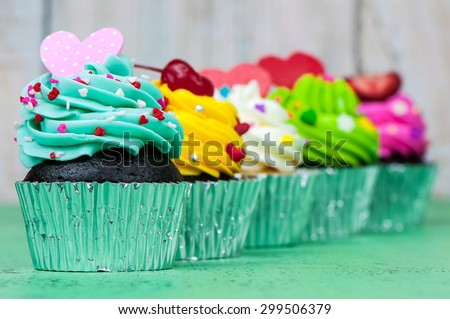 Colorful cupcakes on a wooden background - stock photo