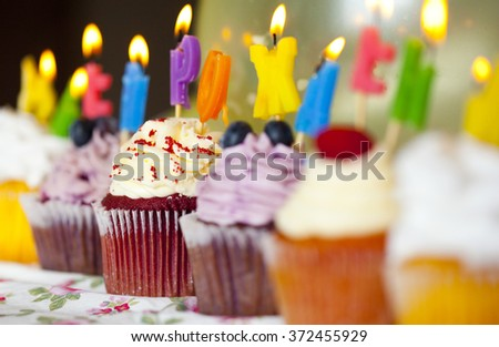 Colorful cupcakes with cream and fresh berries with burning candles