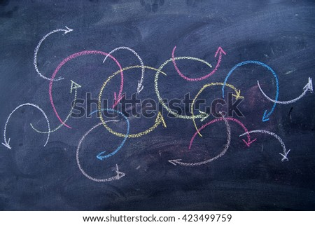 Colorful curved arrows drawn with chalk on blackboard - stock photo