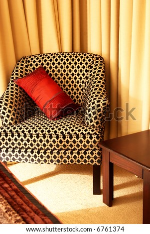 Colorful cushion on a beautiful chair in a guest lodge - stock photo