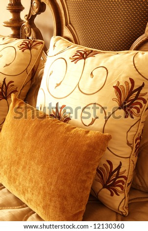 Colorful cushion on a double bed in a guest lodge - stock photo
