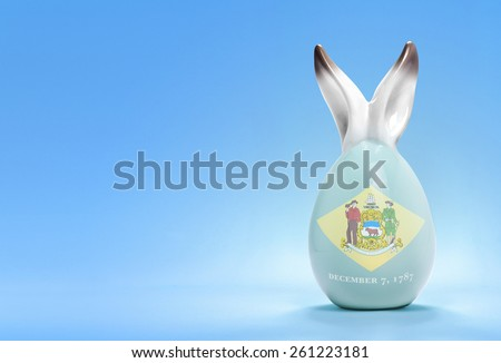 Colorful cute ceramic easter egg with rabbit ears and the flag of Delaware .(series) - stock photo