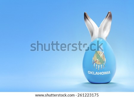 Colorful cute ceramic easter egg with rabbit ears and the flag of Oklahoma .(series) - stock photo