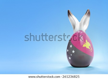 Colorful cute ceramic easter egg with rabbit ears and the flag of Papua New Guinea .(series) - stock photo
