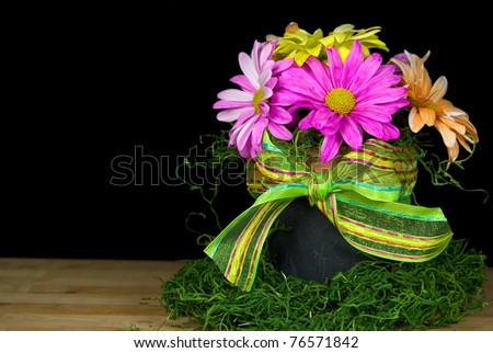 colorful daisies in black pot with bow