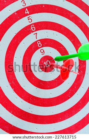 colorful darts hitting a target - stock photo