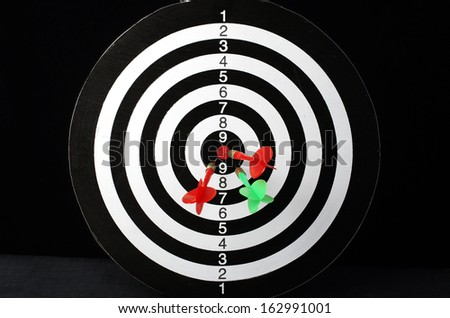 Colorful darts hitting a target, isolated on black  - stock photo