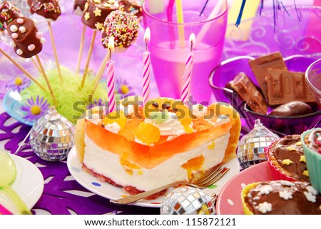 colorful decoration of birthday party table with cake and sweets for child - stock photo