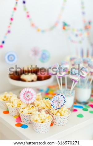 Colorful decoration of kids birthday party table with popcorn and sweets - stock photo