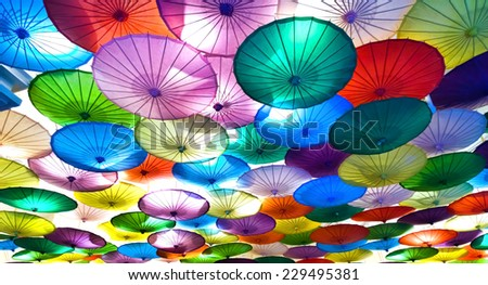 colorful decorative umbrellas hanging from a ceiling - stock photo