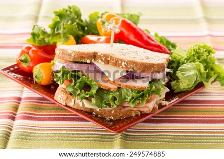 Colorful delicious healthy ham and turkey lunch sandwich on a plate with sweet peppers - stock photo