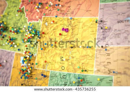 Colorful detail map macro close up with push pins marking locations throughout the United States of America WY Wyoming  - stock photo