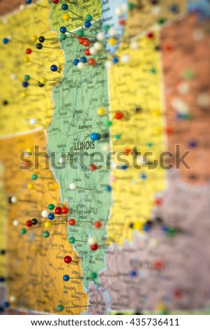 Colorful detail map macro close up with push pins marking locations throughout the United States of America IL Illinois IN Indiana