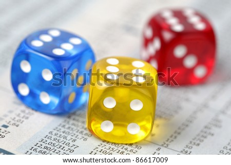 Colorful dice on financial report - stock photo