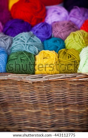 Colorful different wool thread balls in wicker basket. Shot with shallow depth of field - stock photo