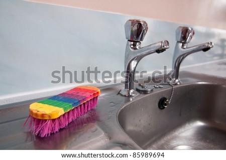 colorful dish brush on the sink - stock photo