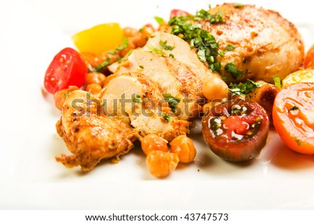 Colorful dish of chicken breast with colorful heirloom cherry tomatoes and garbanzo beans