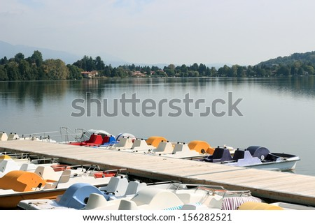 colorful docked pedal boats in Monate Lake , Italy