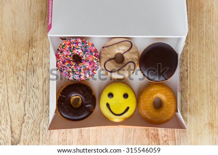 Colorful donuts in box - stock photo