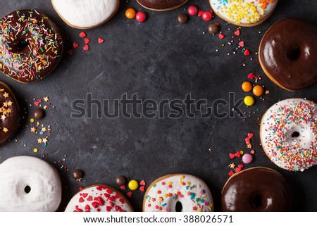 Colorful donuts on stone table. Top view with copy space - stock photo