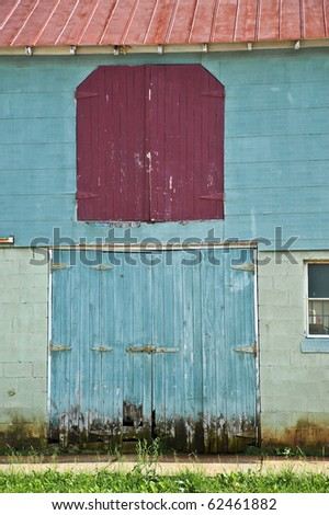 Colorful doors on the side of an old barn. - stock photo