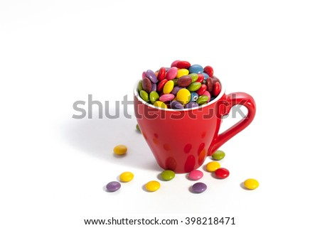 Colorful dragees in small red colored cup on white  - stock photo