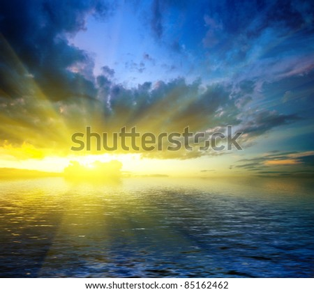 colorful dramatic landscape with water and cloudy sky at sunset - stock photo